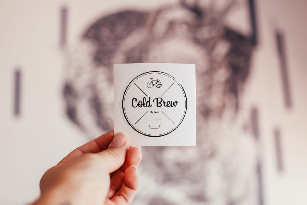 Crop person showing sticker of cafe with inscription