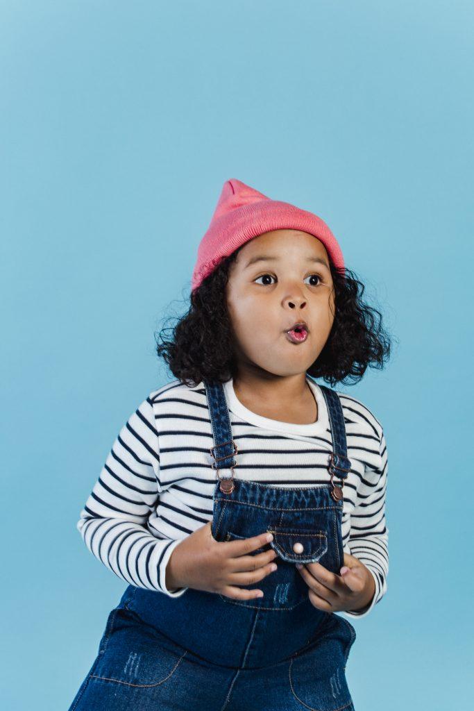 Surprised black girl standing against blue wall