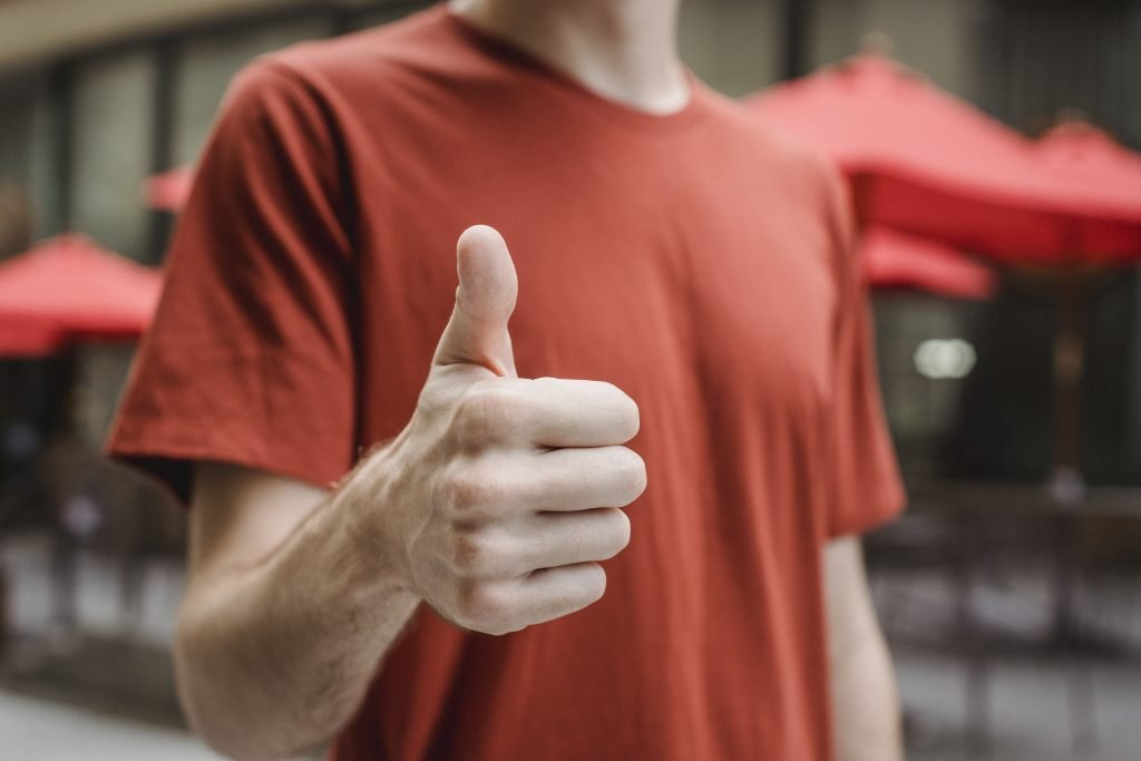 Unrecognizable man showing thumb up on city street